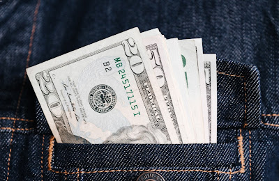 A pocket of a denim jacket with several bills of US currency sticking out.