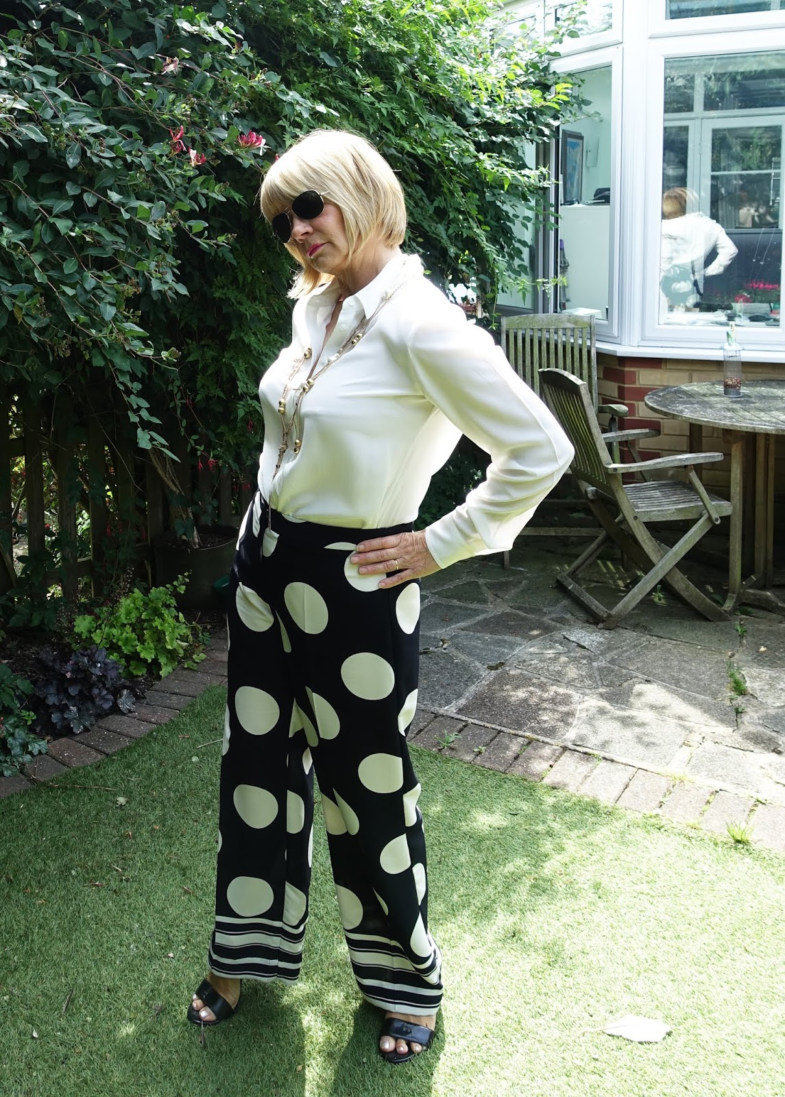 Dramatic circle print wide leg trousers worn with a cream silk blouse from Boden and plenty of gold necklaces.