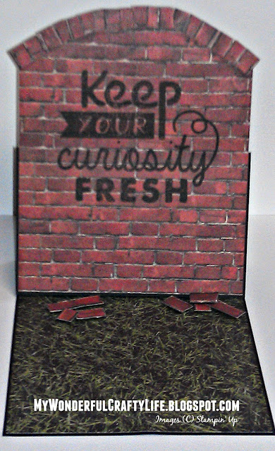 Greeting card to look like a brick wall with fallen bricks on the grass