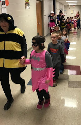 Teacher dressed as a bee holding a young girls hand dressed as Bat Girl