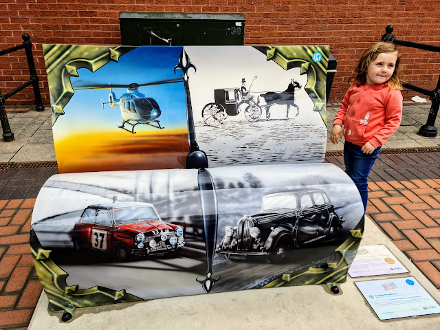 Image of a young girl stood by the bassetlaw nottinghamshire book bench. Thie bench is in the shape of a book and shows various methods of transport through the years. It shows a helicopter, a horse drawn carriage, a red mini and  a black classic car