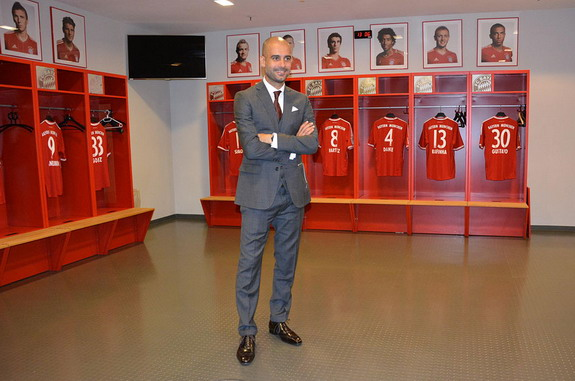 New Bayern Munich coach Pep Guardiola poses in the team locker room inside the Allianz Arena