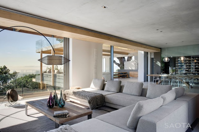 Photo of modern living room interiors with white couch by the large glassy doors to the terrace