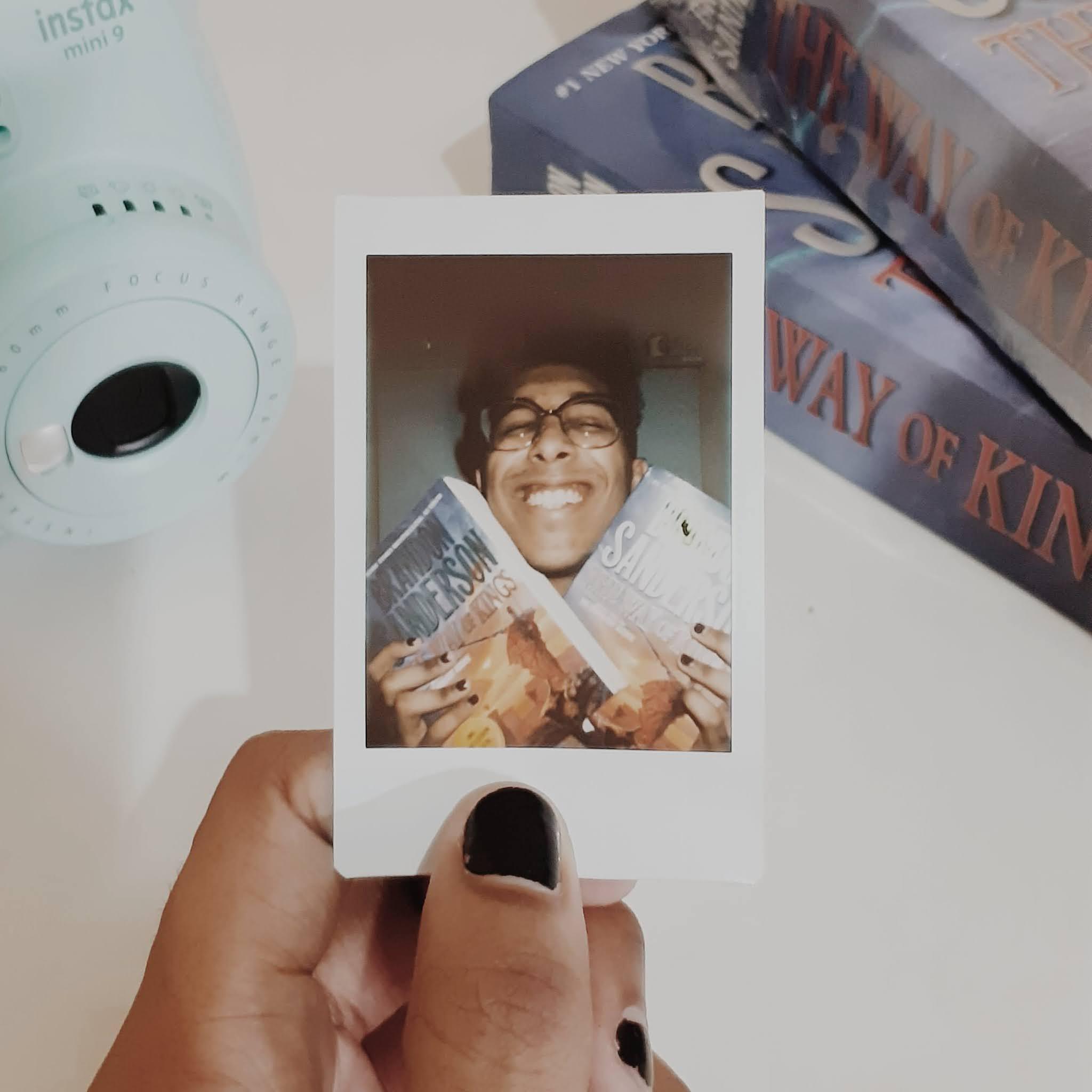 Alec Costa segurando uma polaroid cuja foto ele está feliz com dois exemplares de The Way of Kings.