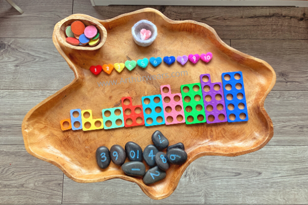 needle felt rainbow hearts with numbers to ten on a wooden tuff tray with numicon, number stones, rainbow wooden discs and loose parts