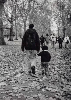 man and boy walk holding hands in hyde park by frederica patmore