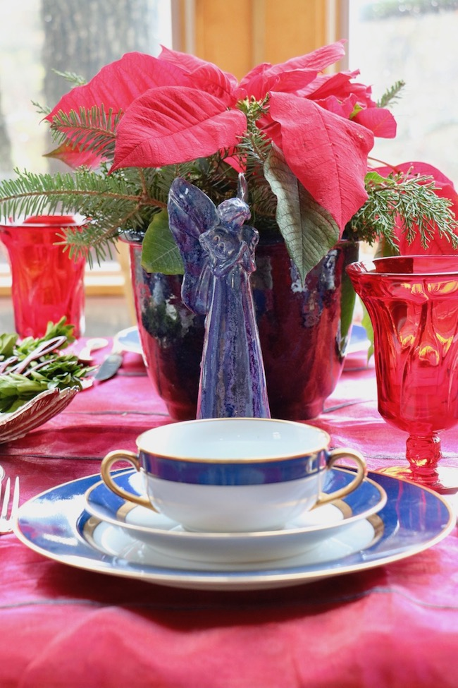 A ceramic blue flower pot holds red poinsettias on a Christmas Red and Navy Blue Table Setting