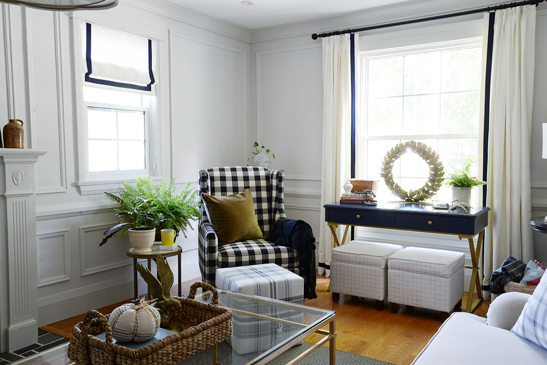 fall living room, fall decor ideas, moulding on walls, roman blind with banding, buffalo plaid arm chair, cube ottoman, ottoman with storage, brass wreath