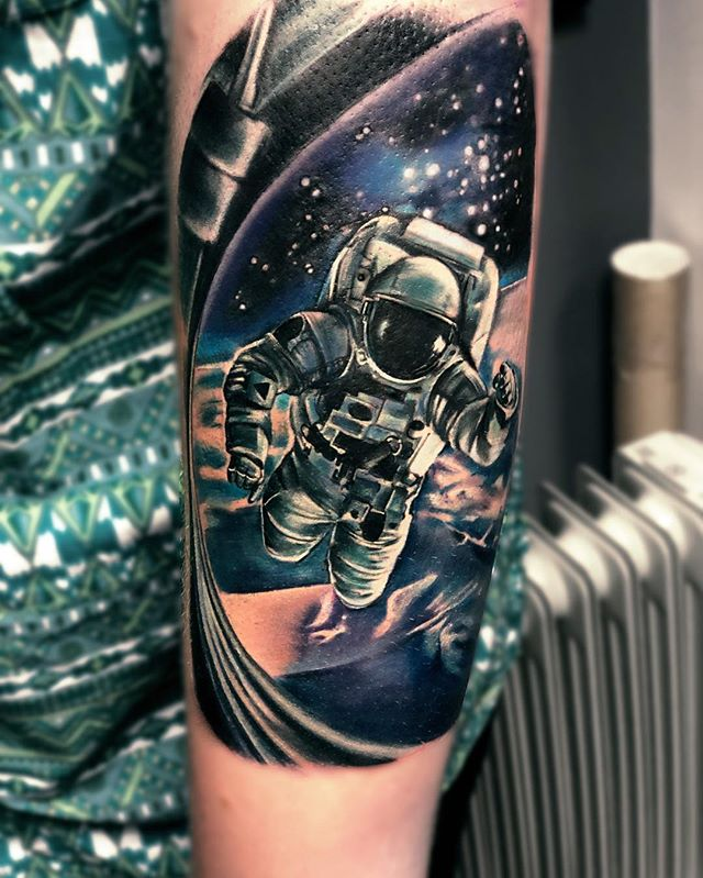 hand astronaut and earth tattoo