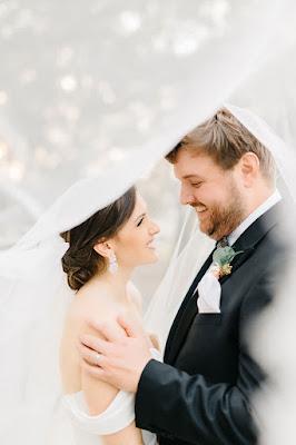 bride and groom smiling under veil
