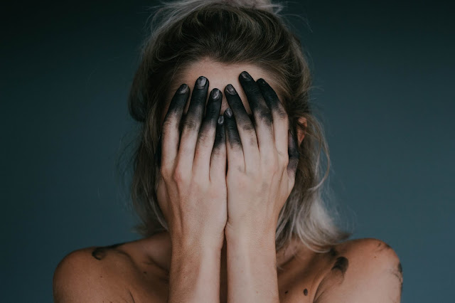 woman hiding her face with both palms