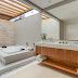 Banheiro com banheira e teto de vidro com cores claras e amadeirado + tijolos de travertino!
