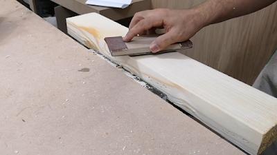 قطعة خشب يتم تنعيمها بواسطة صنفرة عادية