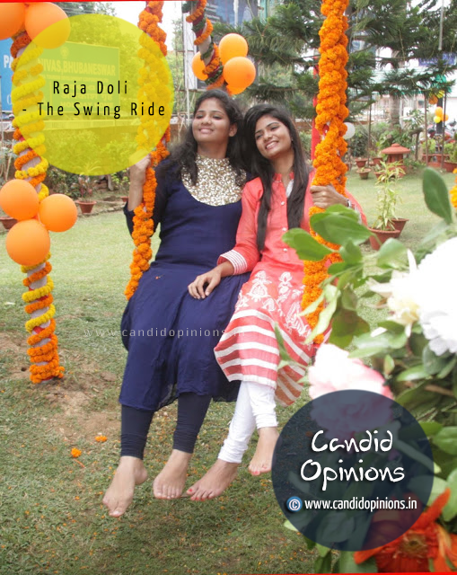 Girls enjoying a swing ride during Raja festival