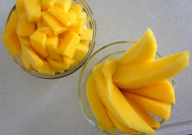 A close up of two bowls filled with mango, one with cubbed mango and one with mango slices