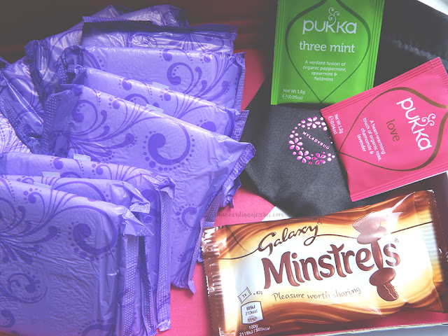 Inside of the Myladybug subscription box featuring always pads, minstrels chocolates, and pukka tea.