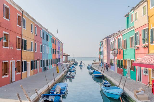"""Bạn sẽ """"đứng hình"""" mất vài giây khi nhìn thấy dãy nhà đầy màu sắc của những ngư dân nằm trong đầm Venetian ở đảo Burano, Ý. Có một bảng màu được quy định nghiêm ngặt cho cư dân kể từ ngày đầu thành lập đảo. Người dân ở đây chỉ có thể sơn màu khác cho ngôi nhà của mình nếu họ xin phép chính phủ."""