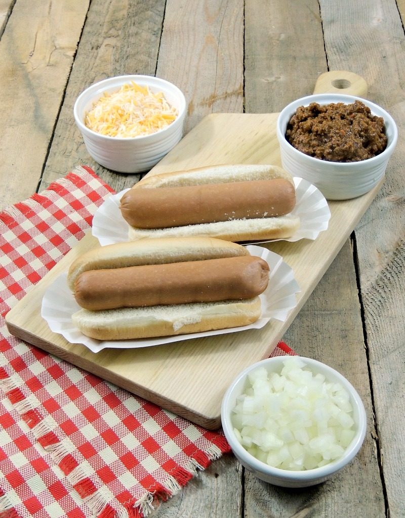 2 plain hot dogs on buns on a cutting board with bowls of chopped onions and shredded cheese on a wooden background with a red and white checkered napkin.