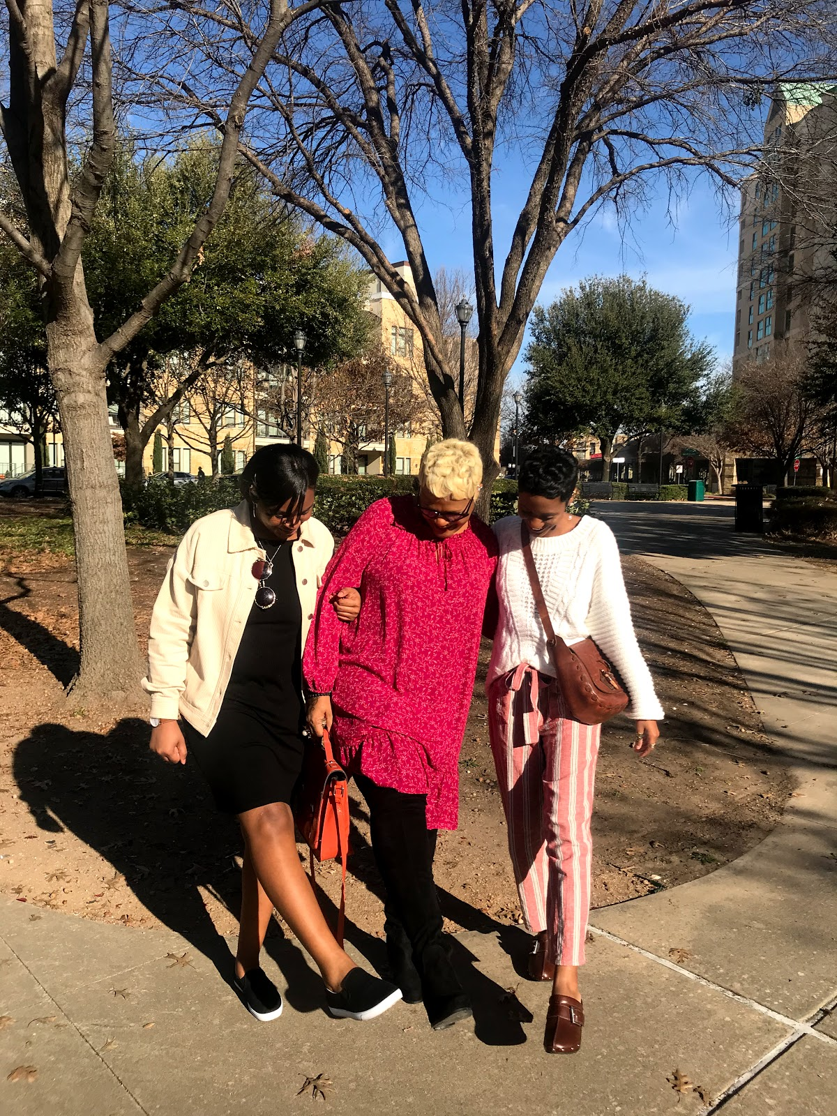Tangie Bell taking pictures of outfits at the park with her daughters
