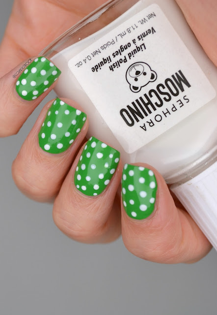 green polka dot nail art holding white nail polish bottle