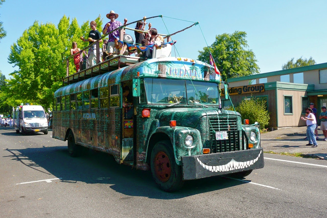 Eugene Celebration parade, float, green hippie bus, samba band on top, downtown traffic