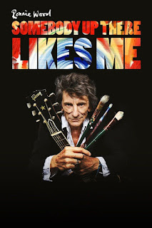 Ronnie Wood holding a guitar stem and artists brushes