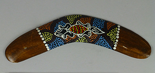 Replica wooden boomerang with painted decoration of a geko