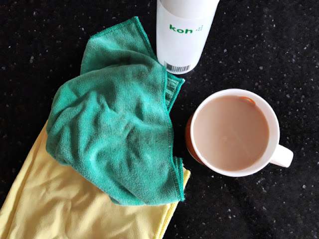 Two cleaning cloths on a granite worktop; one green, one yellow.  A bottle of cleaning spray with the brand name Koh written on the bottle, and an orange mug containing tea