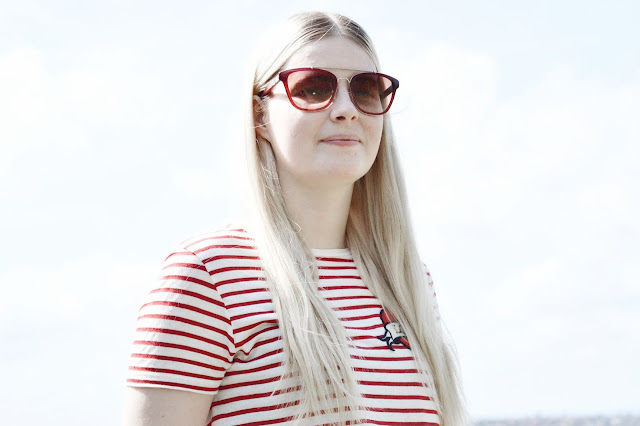 Blonde girl wearing Burberry Sunglasses outside.