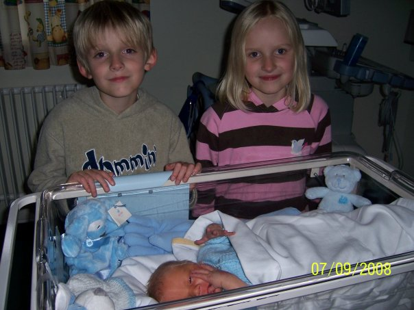 newborn in hospital crib with siblings