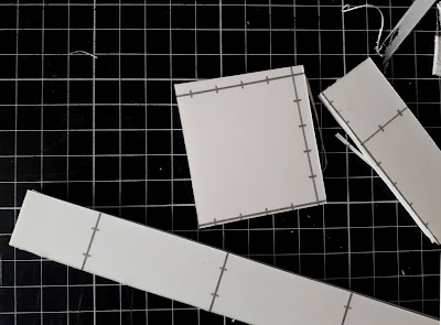 Several pieces of foam core board on a cutting board with guide line markings on them.