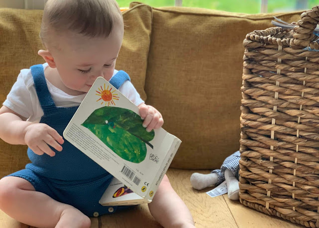baby sitting upright and looking at The Very Hungry Caterpillar book