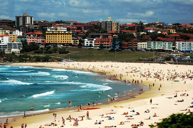 Bondi beach fillled with beachgoers getting a tan, swimming, and surfing