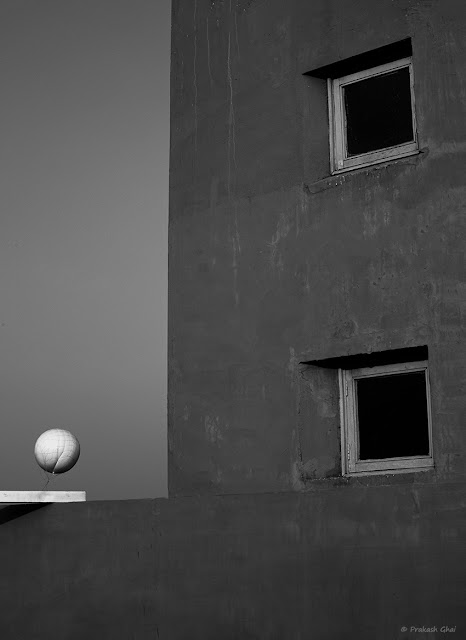 A Black and White Minimal Art Photograph of a White Balloon Vs the Windows at Jawahar Kala Kendra, Jaipur.