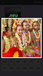 несколько девочек сидят одетые в леи цветные