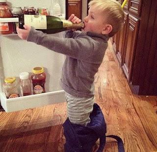 Niño hace como se bebe botella champagne
