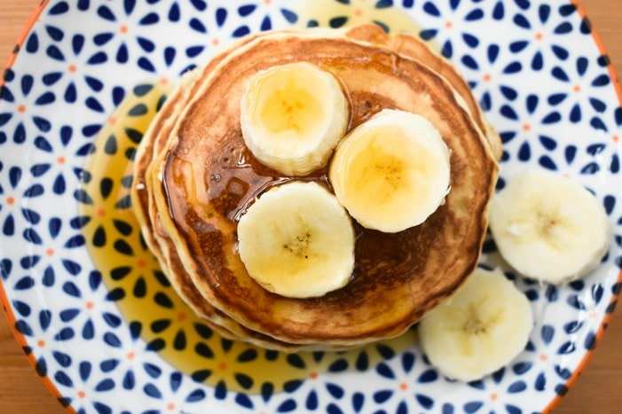 Vegan banana pancakes topped with banana slices and drizzled wit