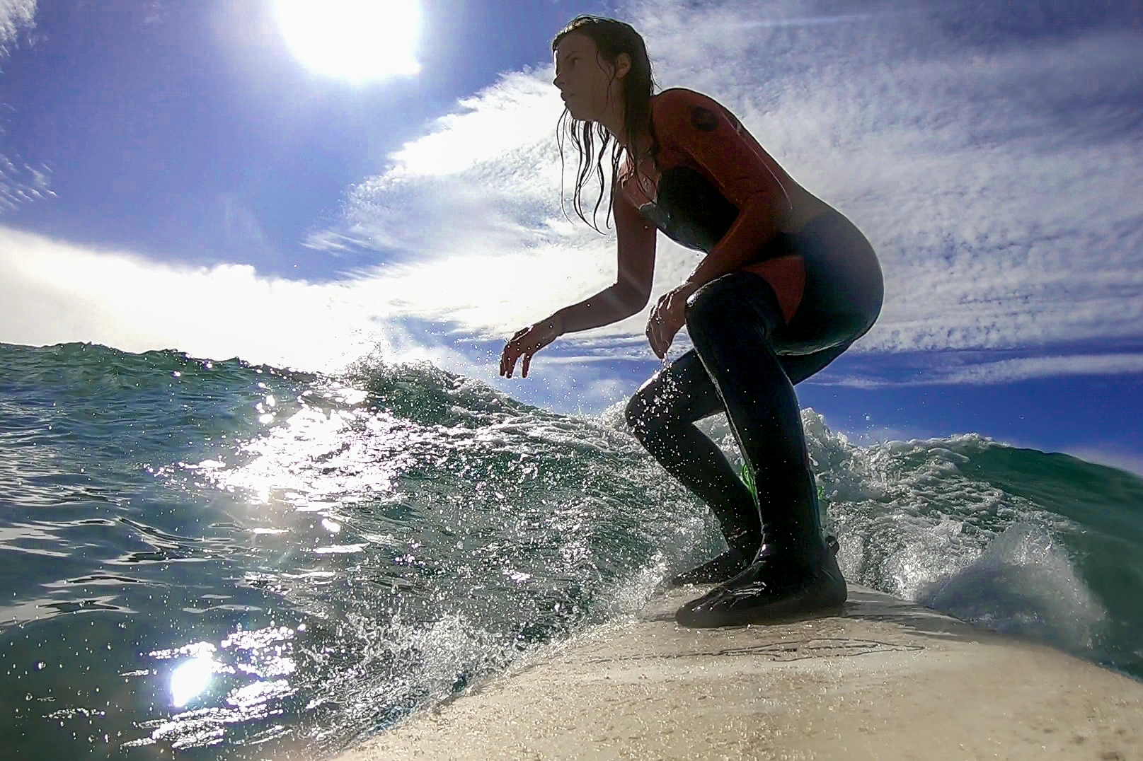 Girl in Cornwall on Sennen beach learning how to surf