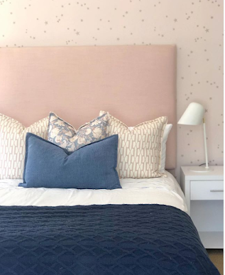 Pink wallpaper with navy bedding in a bedroom