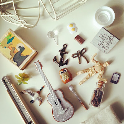 Selection of pieces for use in a one-twelfth scale dollshouse scene, including a glittery guitar, a jar of miniature shells and some metal pieces.