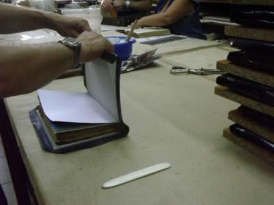 mãos encadernando um livro