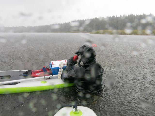 Sukeltaja seisoo SUP-laudan vieressä vedessä sateella