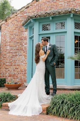 Bride and greem kissing in front of Casa Feliz