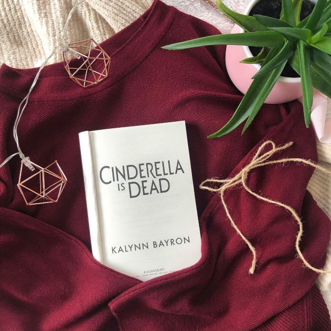 Title page of 'Cinderella is Dead' on a burgundy jumper with a string of fairy lights around it