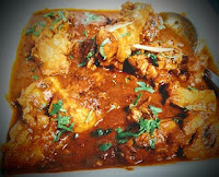 Serving cooked chicken curry with coriander leaves garnish for chicken curry recipe