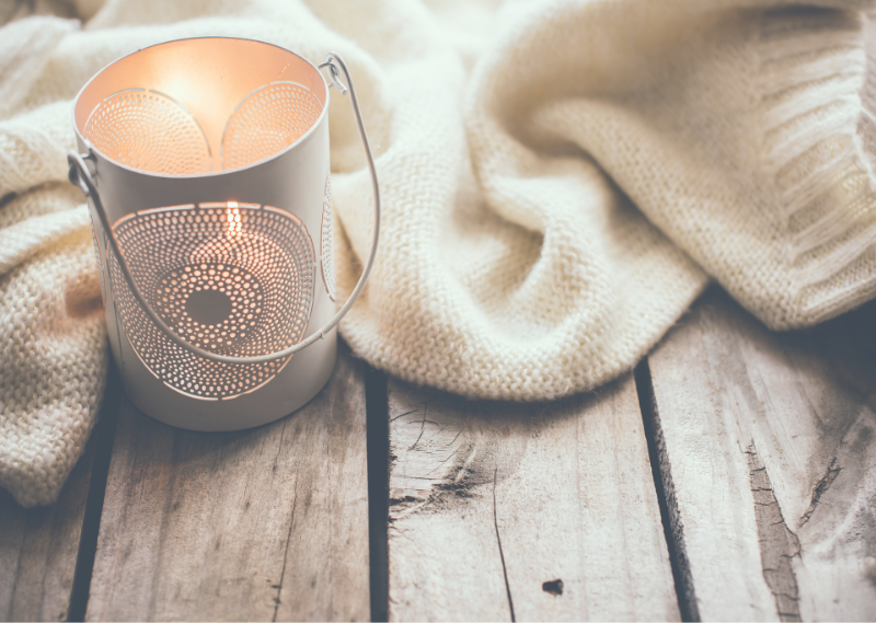 A candle and a jumper in a post about five easy ways to feel cosy at home.