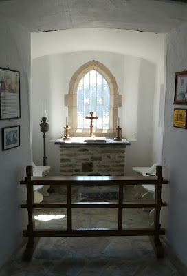Small whitewashed chapel area with window behind.