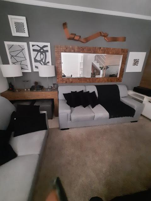 Vou mostrar como ficou a parede atrás do sofá da minha casa depois dessas inspirações. Eu pintei a parede num tom escuro, revesti a moldura do espelho com um mosaico de madeira, fiz uma escultura de parede com alumínio em chapa e pintei com spray cobre. As telas são colagem de placas de MDF que já vieram estampadas. Preferi colocar na tela para dar profundidade e destacar na parede.