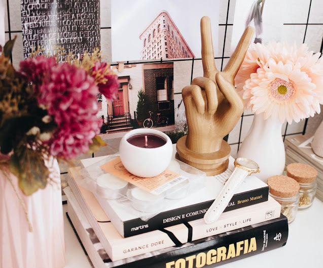 Wooden hand peace sign, sat upon three assorted books.