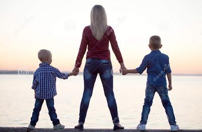 Mãe de mãos dadas com os 2 filhos de frente para um lago